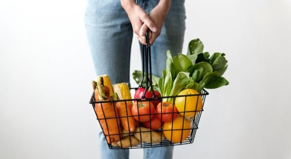 Person in jeans, visible from the waist down, holds a grocery basket in front of them filled with carrots, tomatoes, potatoes and other vegetables.