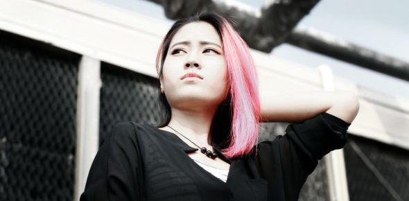 Girl of Asian heritage with pink hair looks into the distance, looking thoughtful with one hand on the back of her neck. She is outside on a sunny day.