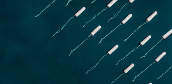 Two diagonal rows of unwrapped tampons sit on a black background.