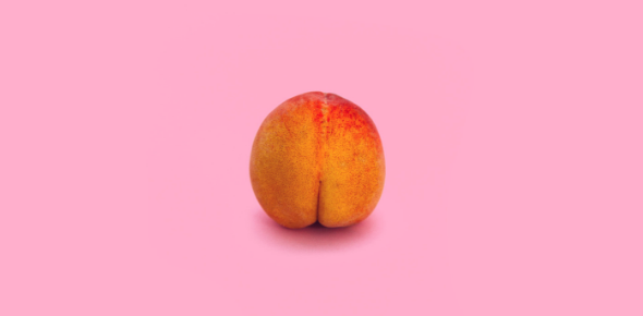 Photo of a peach on a pink background