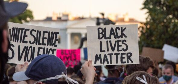 "Group of protesters stand with ""Black Lives Matter"" signs"